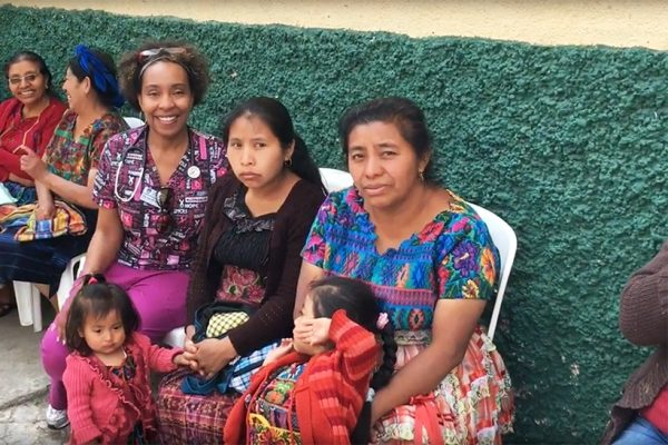 NAU nursing student poses with Guatemalan patients
