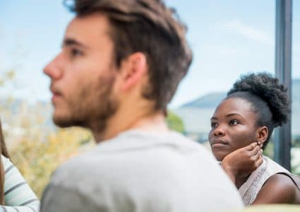 Close up image of a male student and female student looking intently focused on an engaging lecture, with a scenic view of the peaks in the background.
