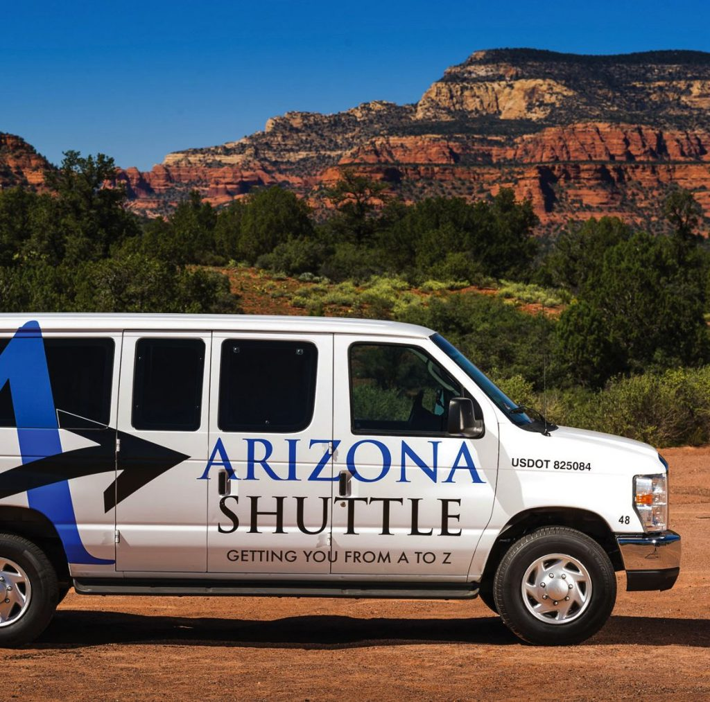 A large, white Arizona Shuttle van with the logo painted on the side is parked in front of desert wilderness and mountains.