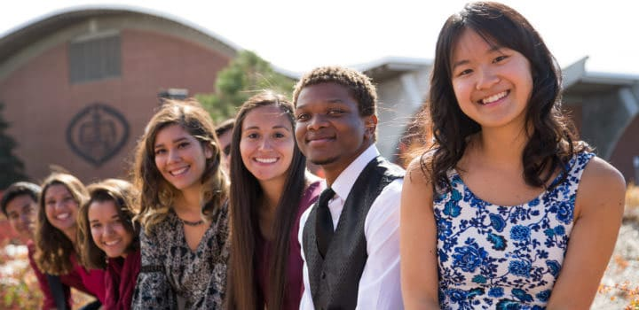 A group of First Scholar program students pose outside with the Field House in the background.