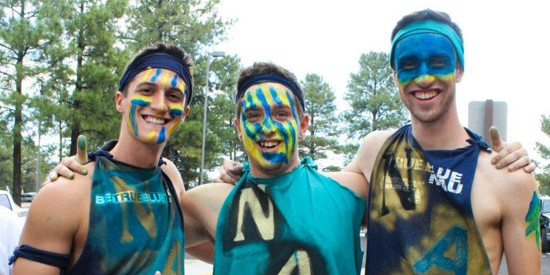 Three NAU students with painted faces and dyed cutaway t-shirts.
