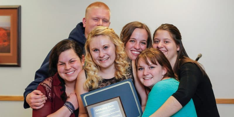A group of students hug each other around a plaque for the A group of students hug each Lumberjack Leaders Institute.