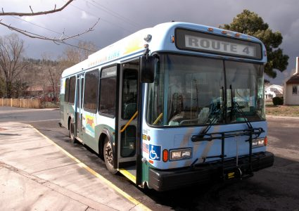 On a cloudy day, a Mountain Line bus waits for students with its doors open at a location off campus.