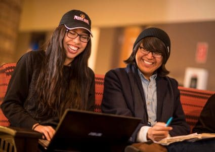 Two students laugh while studying in the Native American Cultural Center.