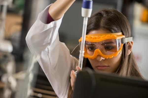 Female student researcher wearing protective orange goggles looking focused while performing research.