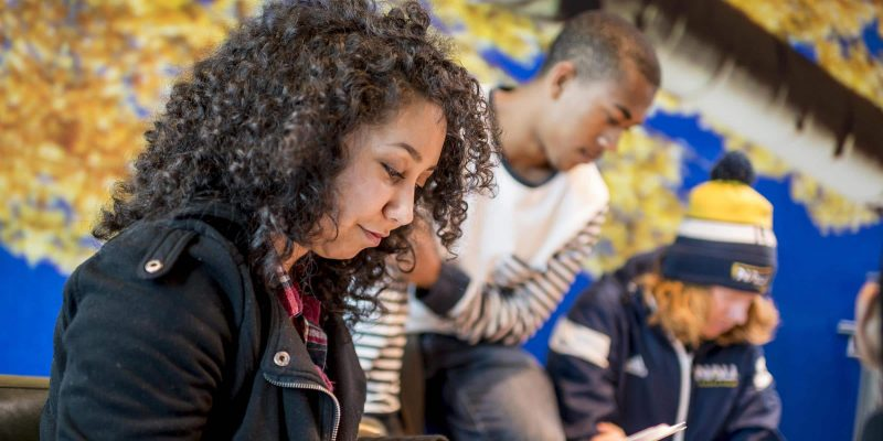 A female student reviews paperwork next to two other students look at something off screen intently.