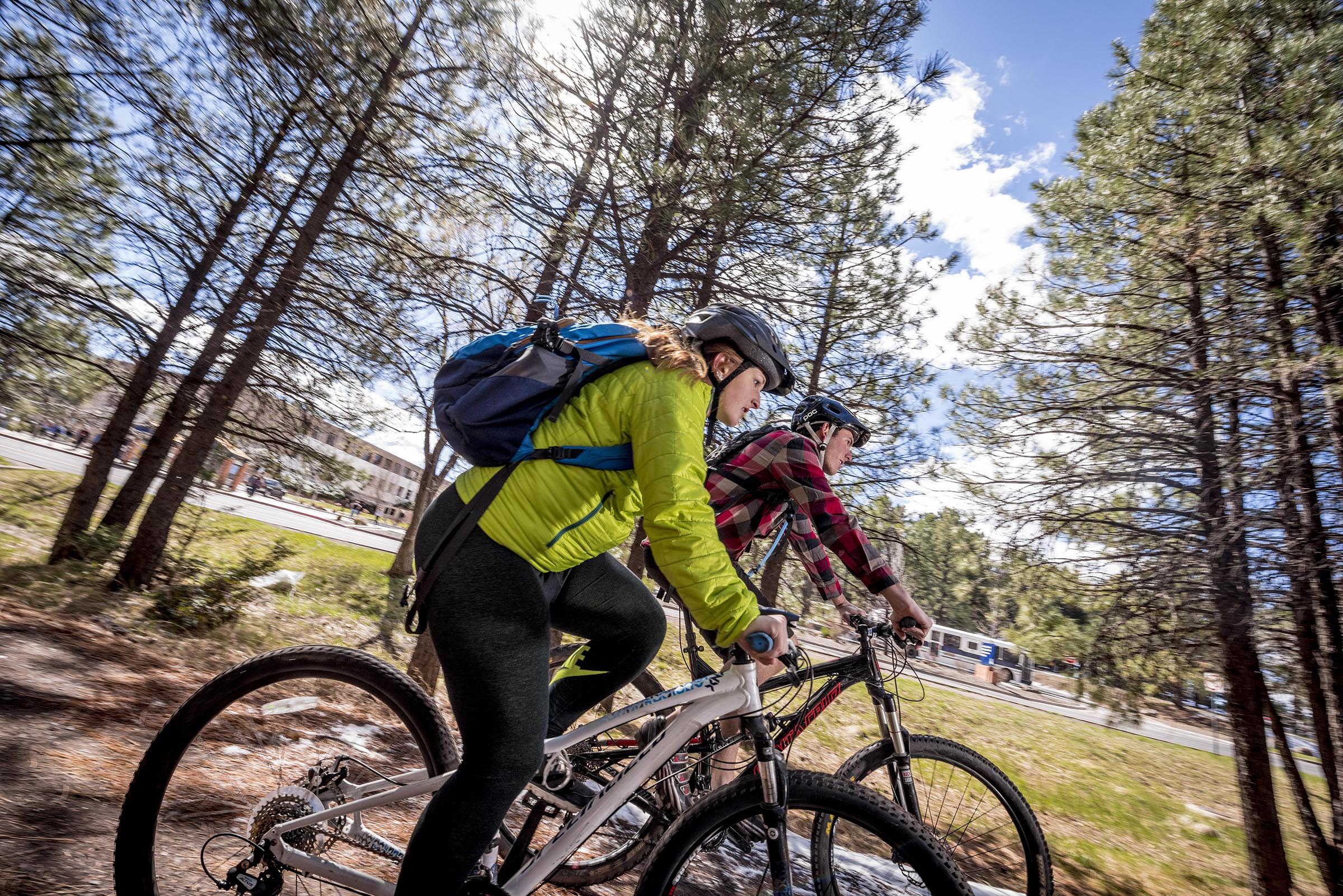 A male and female NAU student ride bikes along a dirt trail among the trees, with the business building on campus to the side of them and in the background of the image.