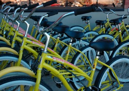 Two rows featuring about 10 newly cleaned Yellow Bikes stand upright on yellow racks.