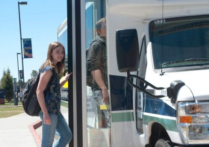 Standing behind a male student, a female student wearing a short sleeve shirt, jeans, and a backpack boards the open doors of an N A U shuttle during a sunny day on campus.