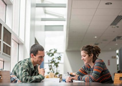 Two NAU students smile while studing together at a table.