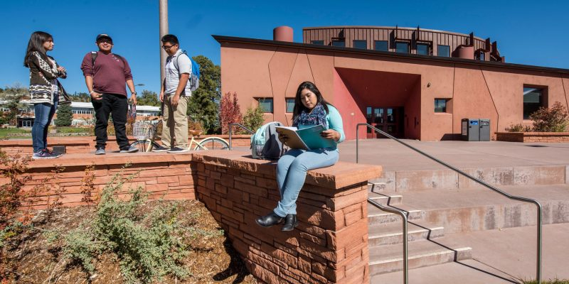An NAU native students sits on a wall studying in front of the NACC.