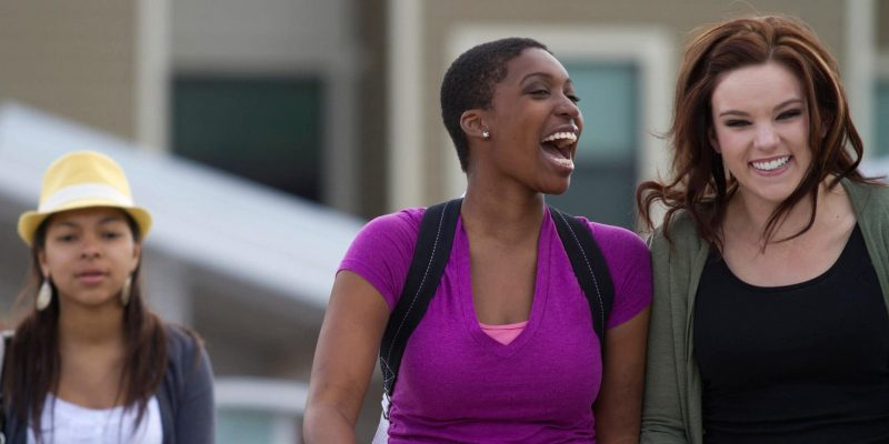 Two students walk on campus, laughing.