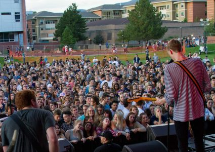 A crowd of dozens N A U students watch a live concert on campus in the evening.
