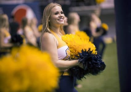 A group of N A U cheerleaders stands on the sideline and watches the game, with the image focused on one in the front, smiling as she holds her blue and gold pom poms.
