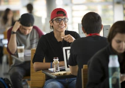 N A U students sit at tables in the Union, with a male student wearing a red backwards hat and glasses in the middle.