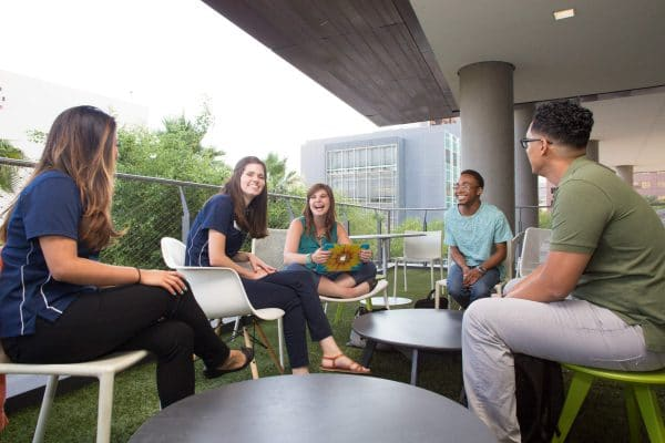 Five N A U students, three female and two male, sit in a circle around tables on a grassy patio, talking and laughing with one another.