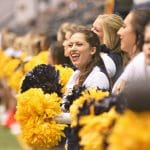 A row of N A U cheerleaders stand side by side, cheering and waving blue and gold pomp oms while they watch a football game.