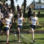 A group of a dozen male cross-country runners race down the track during a competition.