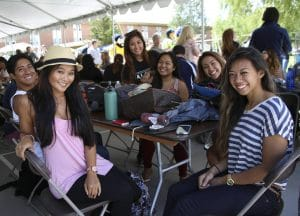Group of five female and one male NAU students, of varying ethnic diversity, sitting at a table under a tent outdoors at an event on the NAU campus.