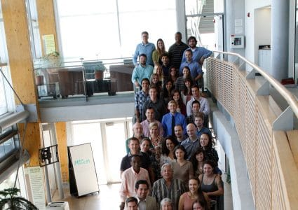 Large group of male and female NAU employees standing on a staircase inside a building on campus looking at the camera and smiling