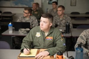 A group of seven male NAU Air Force ROTC cadets sitting at tables in a lecture class taking notes, five students wearing ABUs and two students wearing green flight suits.