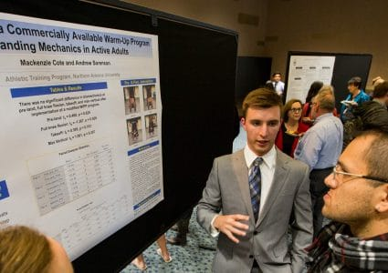 An N A U grad student tries to explain his complex research to event attendees with other presentations and people littered about the large conference room.