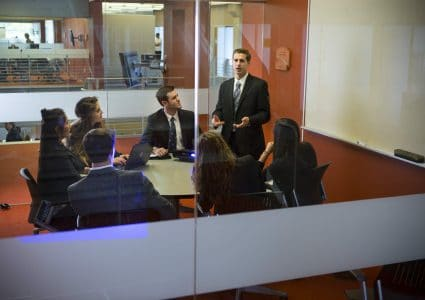 An N A U business student presents and engages peers in a glass-walled conference room in the W A Franke College of Business.