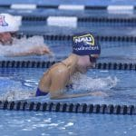 N A U women's swim team member races in front of U of A opponent in blue competition-sized pool.