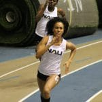 Three track runners sprint next to each other as they race during a competition.