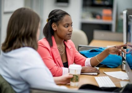 Two female NAU students, one African-American and one Caucasian, sitting at in front of a computer, one student is helping the other with a class assignment.