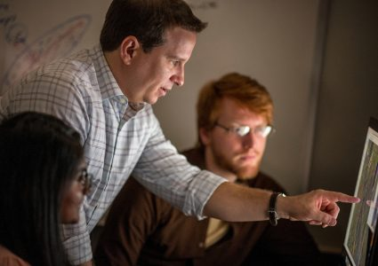 NAU professor with two students looking at a computer screen