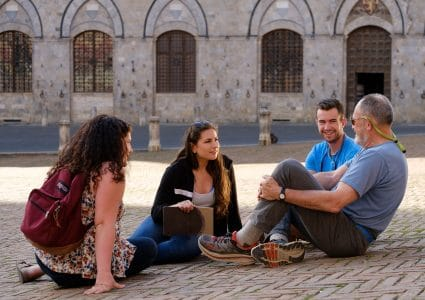 NAU students studying abroad in Italy sit on the ground discussing history.