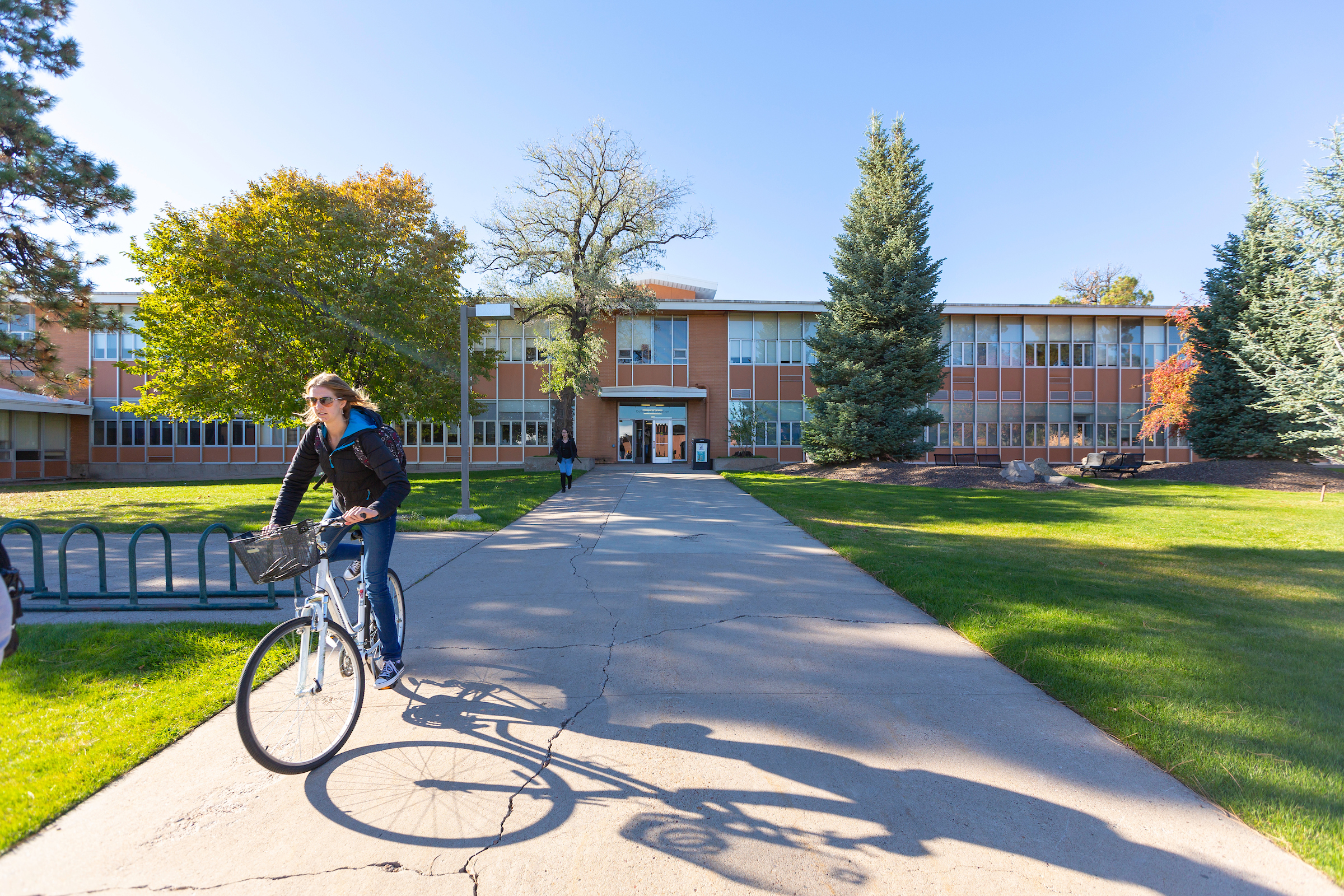 a student leaves the college of education on her bike