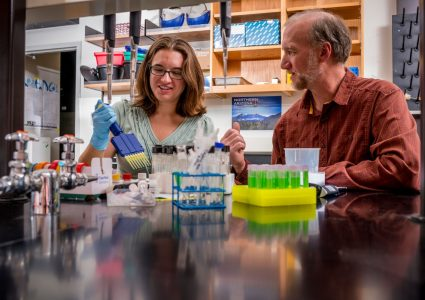 two researchers in a lab surrounded by test tubes