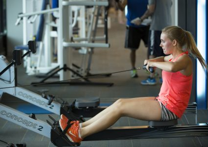 A female wearing pink athletic apparel engages in a rowing machine exercise.