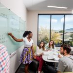 Female instructor writes on a clear white board to teach a group of four N A U students sitting at a circular desk next to a window overlooking the peaks.