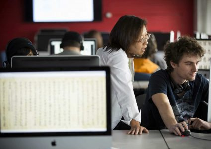 An N A U language professor teaches an eager pupil in computer lab full of students.