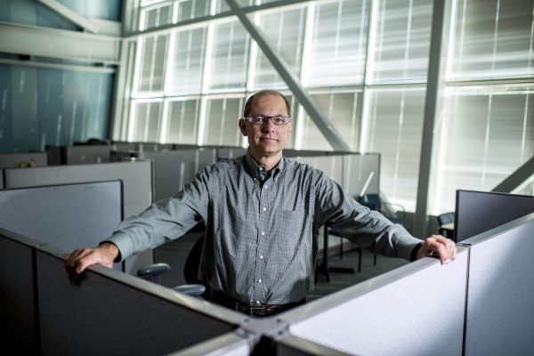 Engineer Bertrand Cambou stands confidently in a computer lab