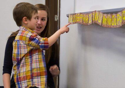 Female N A U student teacher kneels down to help teach the alphabet to an adolescent student.