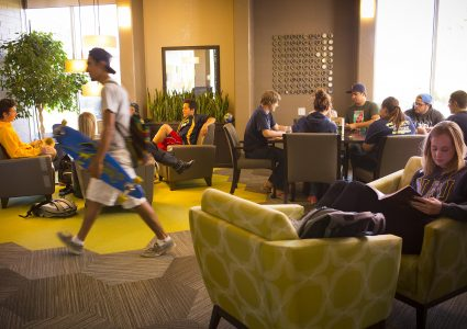 A bustling scene in a housing lounge shows a variety of students visiting, studying, relaxing while reading, and walking through with a long board.