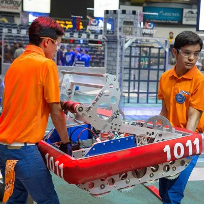 Two high schoolers in orange shirts and safety glasses carry their robot