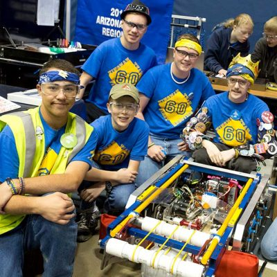 Proud teammates pose with their robot, it's inner workings exposed