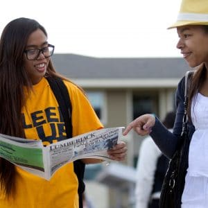 2 students reading lumberjack newspaper