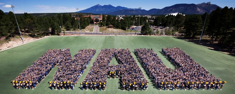 NAU students on the field standing in a formation spelling out NAU