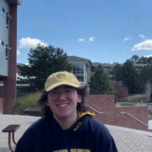 Photo of smiling Chance Willis. Chance is wearing a yellow hat, has brown hair, wears silver wired framed classes, and is wearing a blue sweatshirt.