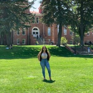 Photo of Elena Garcia standing in green grass in front of Old Main wearing jeans and a yellow shirt