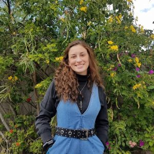 Photo of smiling Maddie Hayes in front of green bush with yellow flowers. Maddie is wearing a jean jumper with long black sleeve shirt.