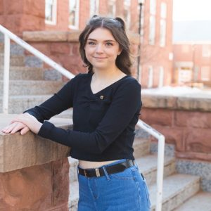 Photo of smiling Rachael Suchy in front of Old Main on NAU campus. Rachael is wearing a black long sleeve shirt with jeans.