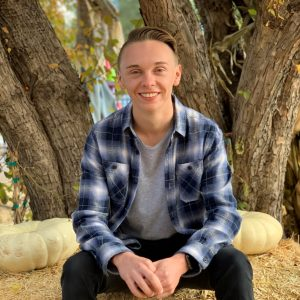 Photo of smiling Trey Fuller sitting on a hay bale in an outdoor area. Trey is wearing a grey shirt with a flannel jackets and jeans.