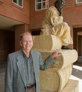 Male professor standing next to statue